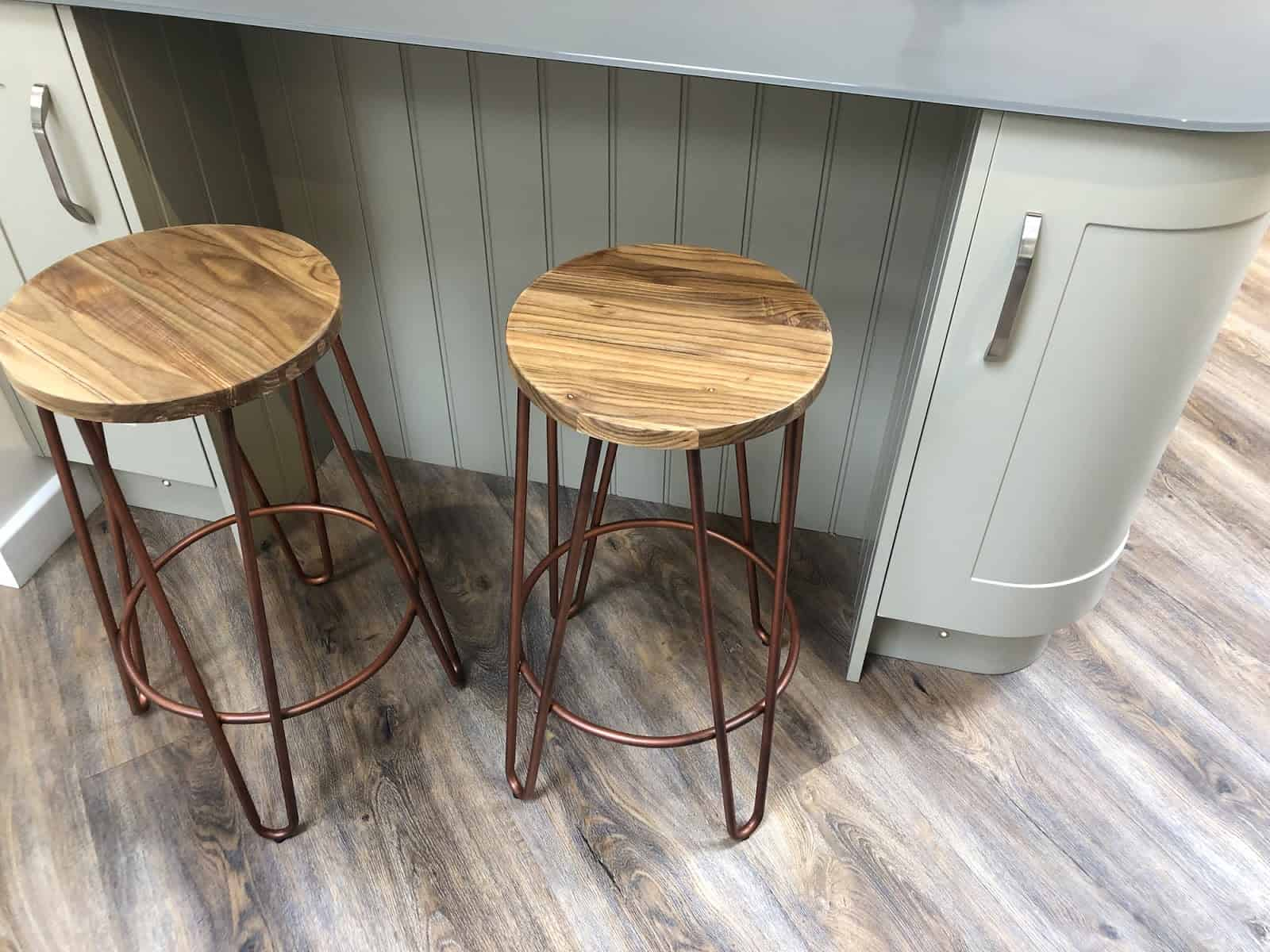 Photo of curved kitchen floor cabinets painted duck egg blue, breakfast bar / kitchen island tongue and groove cladding timber, grey composite corian worktop countertop, oak wood stools with copper coloured metal legs on dark oak effect laminate floors